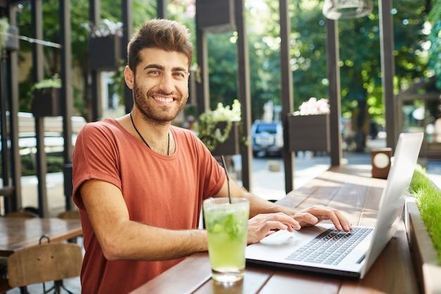 Gut aussehender, attraktiver bärtiger mann, der breit in die kamera lächelt, die lässig gekleidet am holztisch sitzt, limonade trinkt und hochgeschwindigkeitsinternet auf laptop-pc surft. sommertag genießen.
