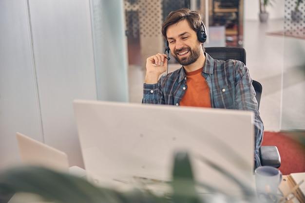 Gut aussehender bärtiger herr im headset, der auf das laptop-display schaut und lächelt, während er mit computer am tisch sitzt sitting