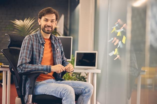 Gut aussehender bärtiger mann, der bei der arbeit in einem modernen büro in die kamera schaut und lächelt