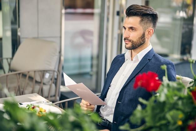 Gut aussehender bärtiger mann, der im café sitzt und tief in gedanken versunken ist, während er auf kaffee wartet?