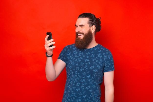 Gut aussehender bärtiger mann schaut auf das telefon und spricht mit jemandem über rotem hintergrund.
