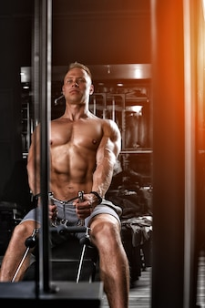 Gut aussehender bodybuilder, der schwere übungen für den rücken auf einem simulator macht. athletischer körper, vorbereitung auf die sommersaison. fitness-motivation. kopieren sie platz, sportbanner.