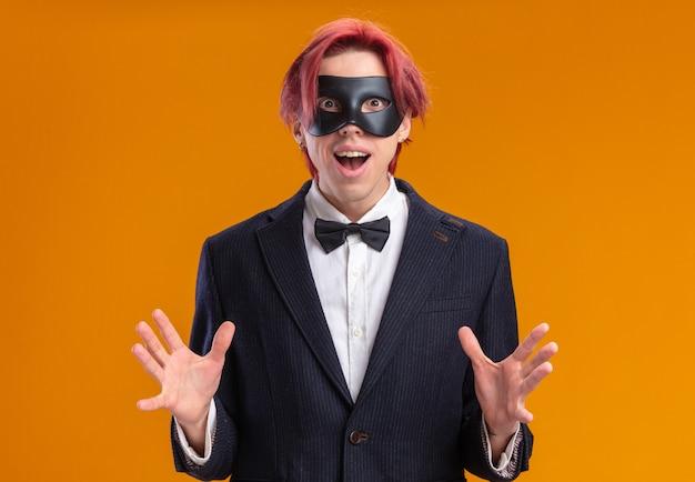 Gut aussehender bräutigam im anzug mit fliege und maskerade-maske, der glücklich und aufgeregt aussieht