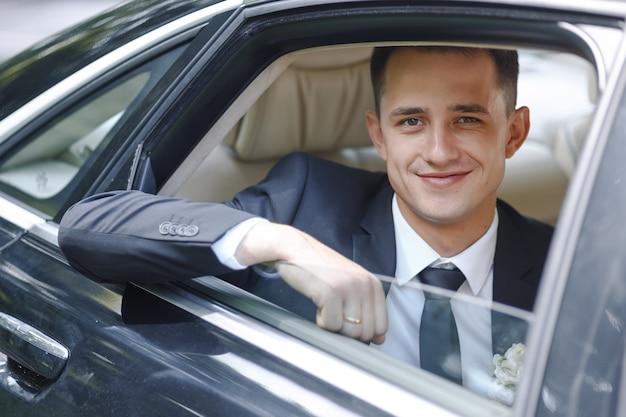 Gut aussehender bräutigam kommt aus einem auto