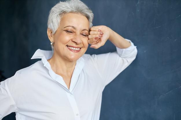 Gut aussehender erfolgreicher weiblicher manager mittleren alters im weißen hemd, das aufwirft, gesicht berührt und lächelt