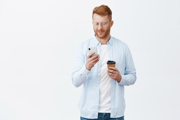 Gut aussehender europäischer rothaariger mann mit der borste in den gläsern und im hemd, die zeit im smartphone überprüfen, während sie über graue wand stehen und auf freund warten, kaffee trinken, handybildschirm betrachten, lächeln