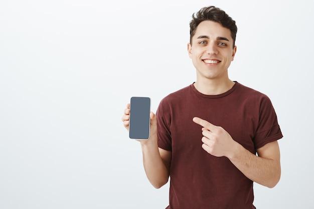 Gut aussehender freundlicher männlicher verkäufer im lässigen roten t-shirt, das ein neues smartphone zeigt