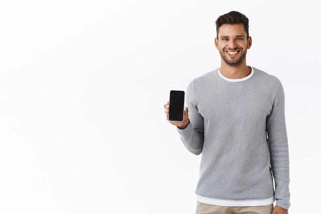 Gut aussehender fröhlicher junger mann fördert die smartphone-anwendung, hält ein telefon oder etwas auf dem mobilen bildschirm und lächelt zufrieden