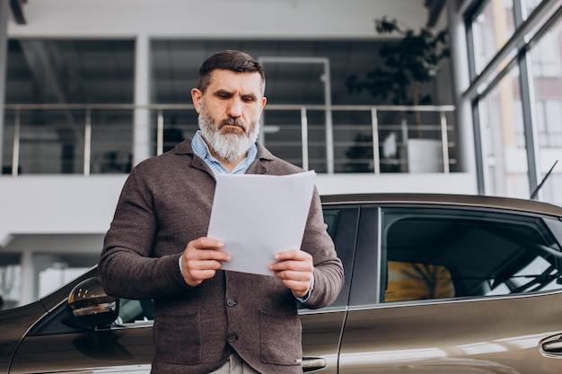 Gut aussehender geschäftsmann, der dokumente über autovermietung liest