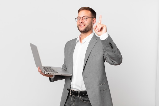Gut aussehender geschäftsmann, der einen laptop hält