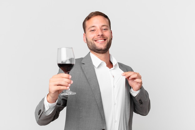 Gut aussehender geschäftsmann, der einen wein trinkt