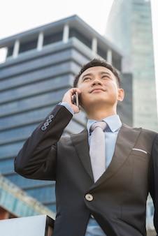 Gut aussehender geschäftsmann, der handy in seinem firmengebäude spricht, modell ist ein asiatischer mann