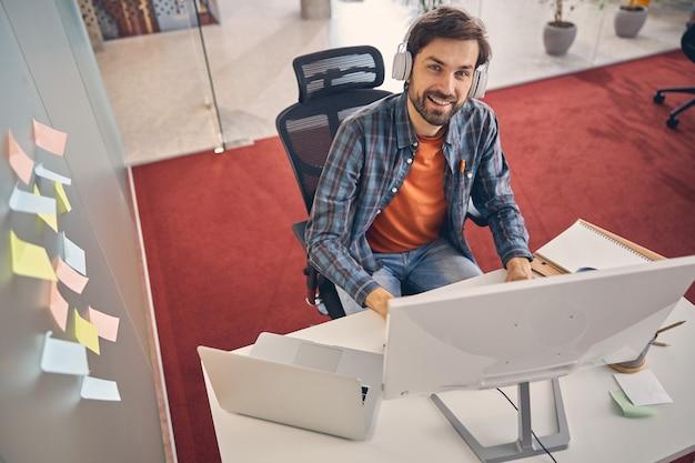 Gut aussehender geschäftsmann, der in die kamera schaut und lächelt, während er mit computer und laptop am tisch sitzt sitting