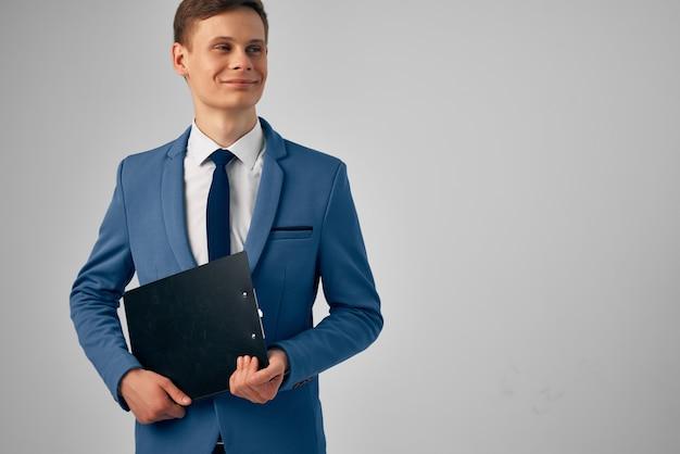 Gut aussehender geschäftsmann im anzug mit dokumenten in den händen des studiomanagers. foto in hoher qualität