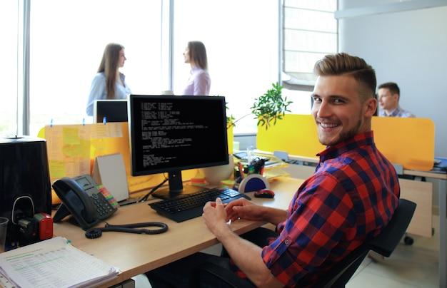 Gut aussehender geschäftsmann in freizeitkleidung vor dem hintergrund seiner partner im kreativbüro