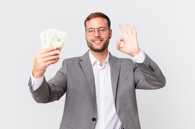 Gut aussehender geschäftsmann mit dollarbanknoten