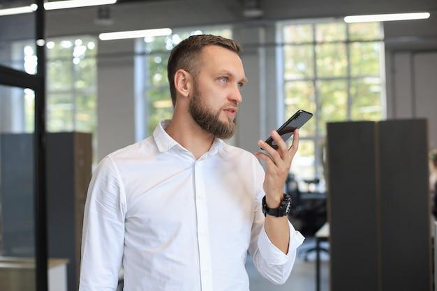 Gut aussehender geschäftsmann mit einer spracherkennungs-app im büro.