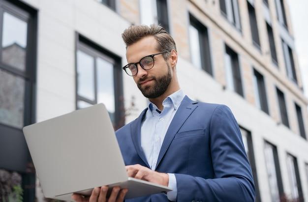 Gut aussehender geschäftsmann mit laptop-computer, der online nach etwas sucht erfolgreiches geschäft