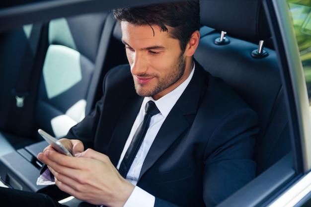 Gut aussehender geschäftsmann mit smartphone im auto