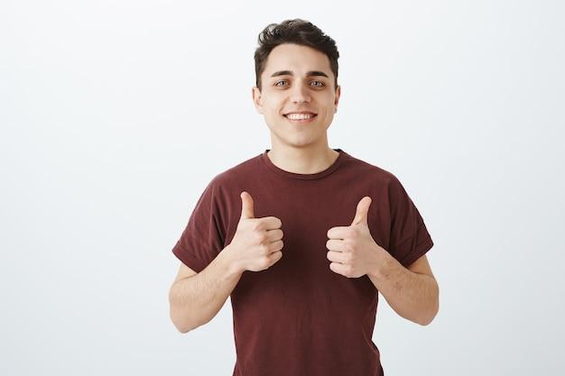 Gut aussehender glücklicher kaukasischer mann im lässigen outfit mit daumen hoch