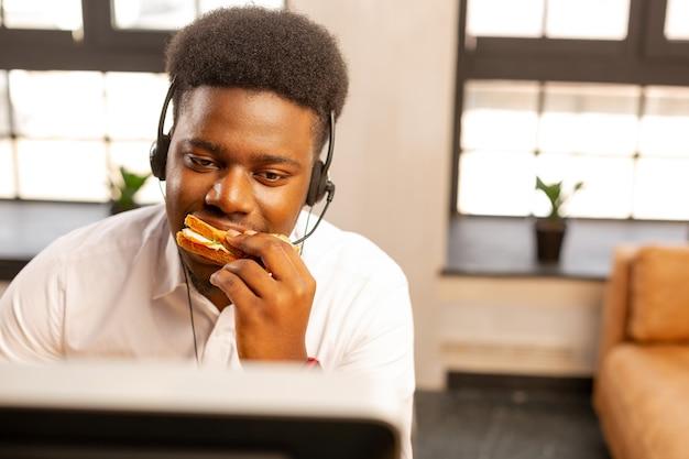 Gut aussehender, gutaussehender mann, der bei der arbeit einen leckeren snack zu sich nimmt?