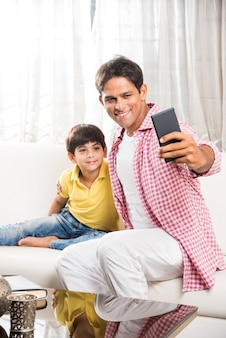 Gut aussehender indischer asiatischer verspielter vatersohn, der eine gute zeit zu hause hat, während er über dem sofa sitzt