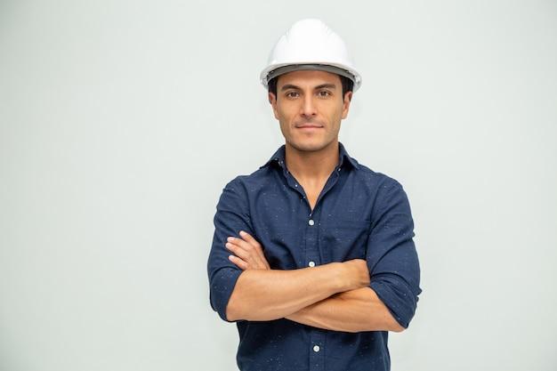 Gut aussehender industrieingenieur des mannes, der einen weißen helm trägt, der auf weißem hintergrund solated wird