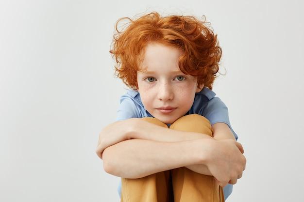 Gut aussehender junge mit lockigem rotem haar, der beine mit händen hält und mit entspanntem und ruhigem ausdruck zur seite schaut.
