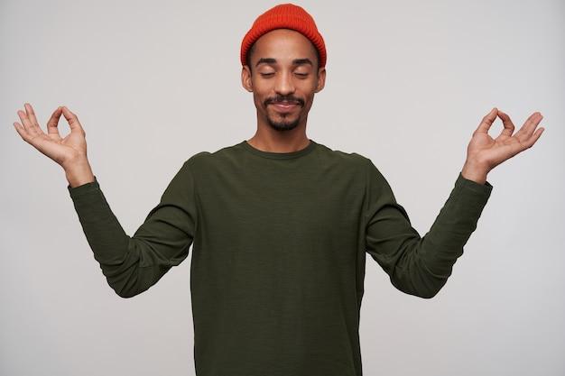 Gut aussehender junger dunkelhäutiger brünetter mann mit bart, der mit geschlossenen augen meditiert und finger im mudra-zeichen faltet, roten hut und khaki-pullon auf weiß tragend