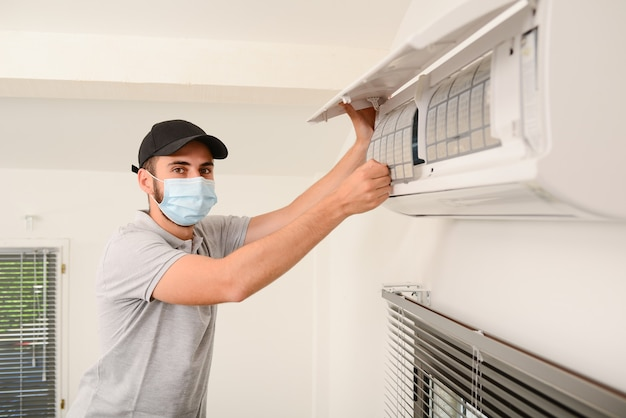 Gut aussehender junger elektriker mit chirurgischer maske, der luftfilter an einer inneneinheit der klimaanlage in einem kundenhaus reinigt