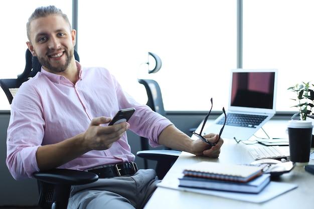 Gut aussehender junger geschäftsmann im hemd mit smartphone und lächelnd beim sitzen im büro.