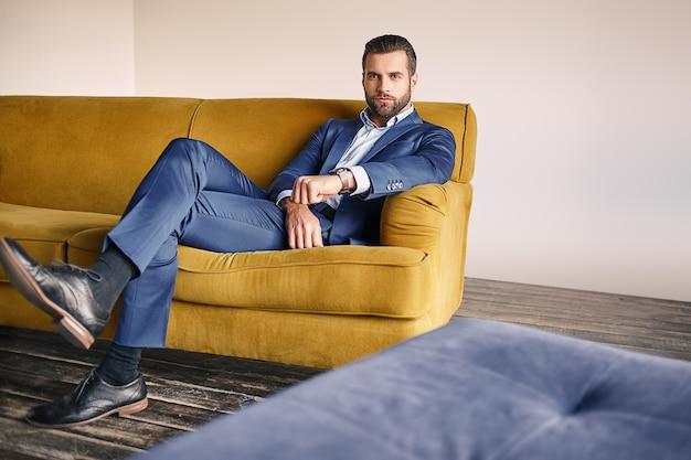 Gut aussehender junger geschäftsmann in einem stylischen anzug entspannt sich auf dem sofa und schaut zu