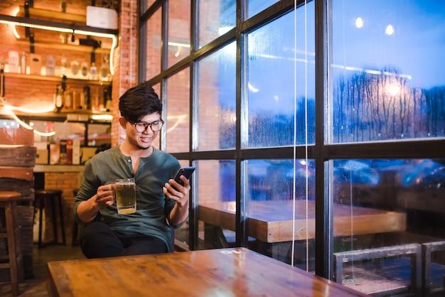 Gut aussehender junger mann asiaten arbeiten an laptops, schauen sich videos auf smartphones an, halten handys in der hand und surfen mit highspeed-5g im internet.