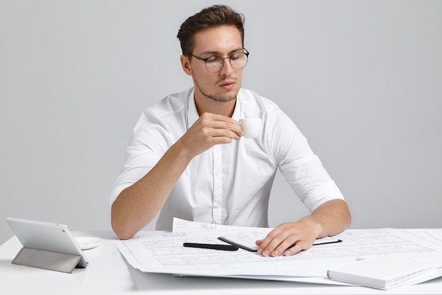 Gut aussehender junger mann betrachtet tasse als getränke heißen kaffee oder tee, arbeitet bei zukünftigen projekt, entwickelt neue strategie, verwendet modrn gerät, sitzt drinnen am arbeitsplatz. menschen, beruf, berufsbild