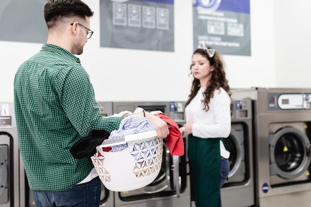 Gut aussehender junger mann, der wäsche im waschsalon macht.