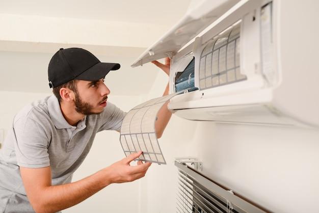 Gut aussehender junger mann elektriker, der luftfilter an einer inneneinheit der klimaanlage in einem kundenhaus reinigt