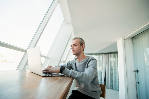 Gut aussehender junger mann in lässigem grauem sweatshot schaut in den bildschirm seines computers