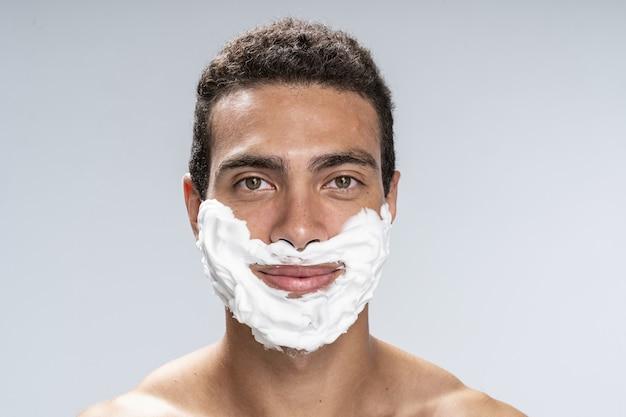 Gut aussehender junger mann mit rasierschaum im gesicht