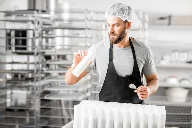 Gut aussehender käser, der die qualität eines käses überprüft, der auf dem kleinen produzierenden bauernhof arbeitet