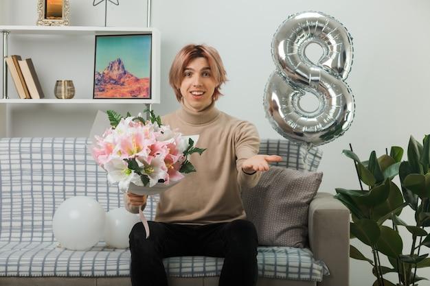 Gut aussehender kerl am glücklichen frauentag mit blumenstrauß auf dem sofa im wohnzimmer sitzend