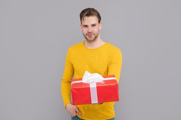 Gut aussehender kerl im gelben pullover halten geschenkbox grauen hintergrund, schenken.