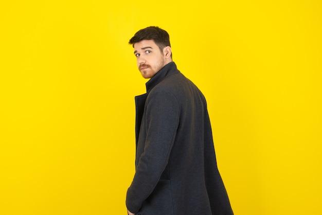 Gut aussehender kerl in freizeitkleidung auf einem gelb.