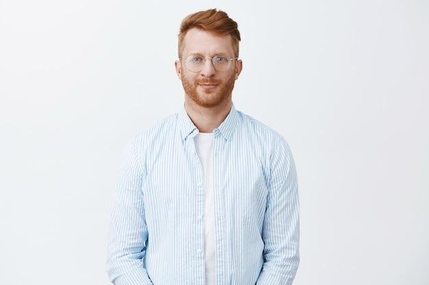 Gut aussehender kreativer und kluger rothaariger männlicher unternehmer, der im freizeithemd und in der brille über grauer wand steht, freundlich lächelt und mit nachdenklichem, entschlossenem blick blickt