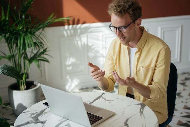 Gut aussehender lächelnder mann freiberufler mit laptop mit videoanruf von zu hause aus arbeiten working