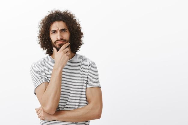 Gut aussehender männlicher männlicher sportler mit afro-haarschnitt, stirnrunzelndem und berührendem bart, während er eine entscheidung trifft, während des bürotreffens intensiv und konzentriert ist