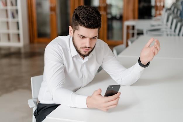Gut aussehender mann am arbeitsplatz mit telefon