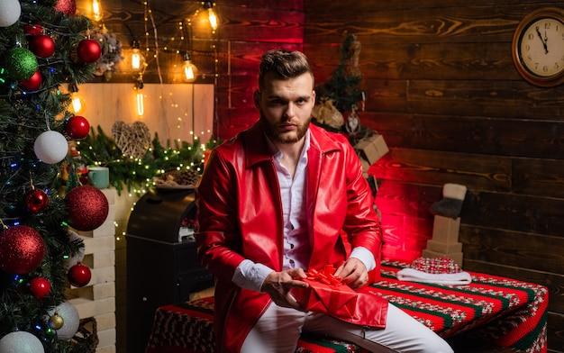 Gut aussehender mann am vollen weihnachtlich dekorierten hintergrund. sexy heißer junge, der weihnachtsgeschenk in seiner hand hält und rote lederjacke trägt. heiligabend. urlaub. innen. heim.