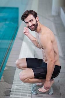 Gut aussehender mann auf einer gewichtsskala am pool
