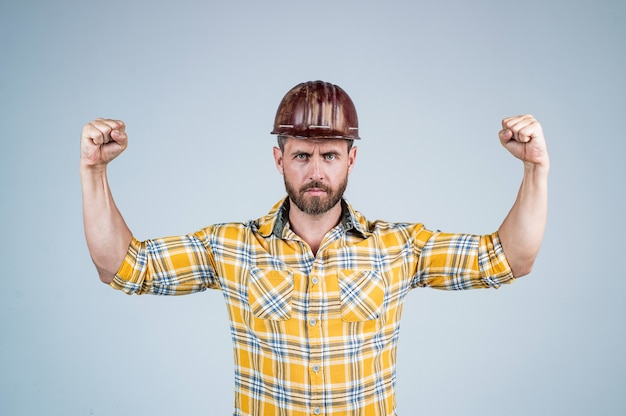 Gut aussehender mann baumeister im bau schutzhelm und kariertes hemd demonstarte power auf der baustelle, männliche stärke.