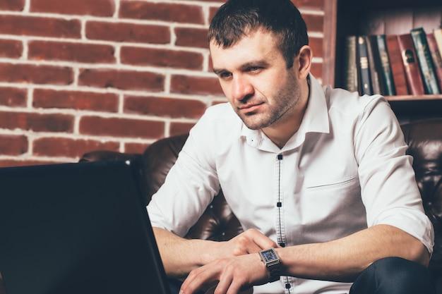 Gut aussehender mann betrachtet den laptopschirm im bürokabinett. er ist im business-anzug in schwarz-weißen farben gekleidet